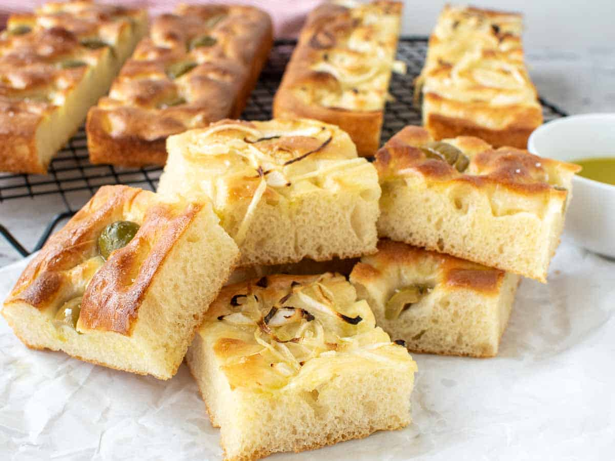 squares of focaccia with green olives and onions cooked in on top