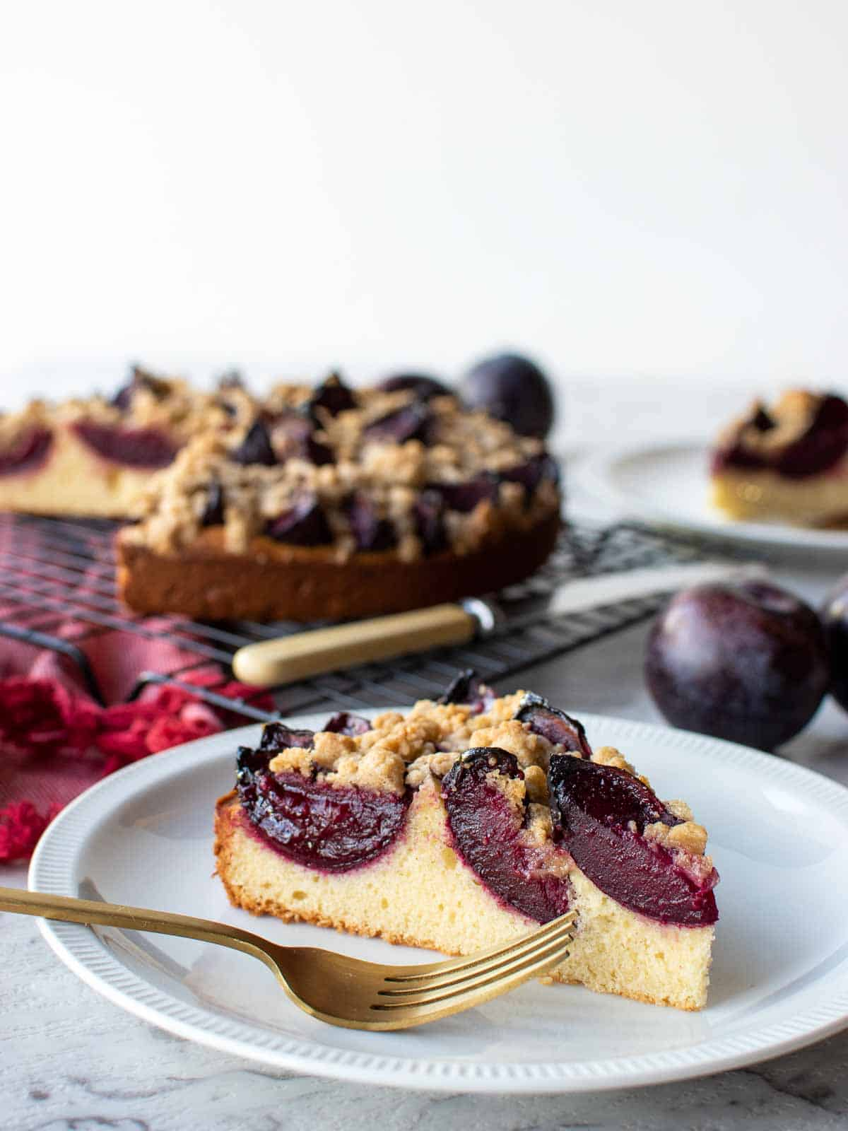 slice of plum cake on white plate with whole cake in the background.