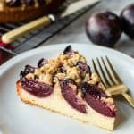 slice of plum cake on white plate with gold fork.