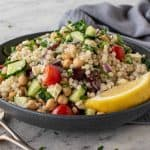 bowl of couscous salad with fork and spoon in the front and grey towel in the background.