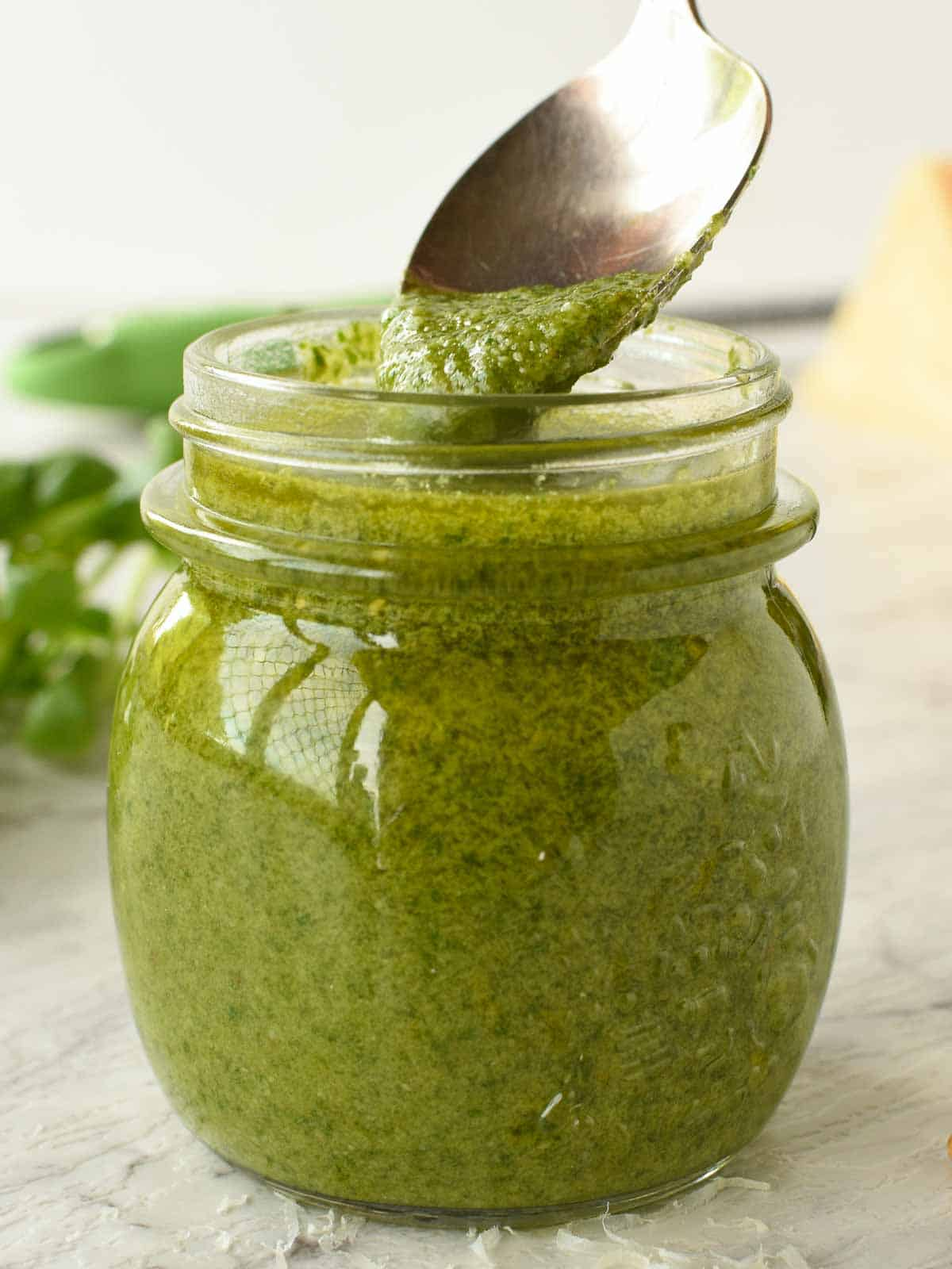 glass jar of pesto with a spoonful being spooned out, fresh basil in the background