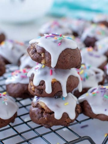 close up of three chocolate cookies with white frosting and sprinkles stacked with extra cookies around all on a wire rack.