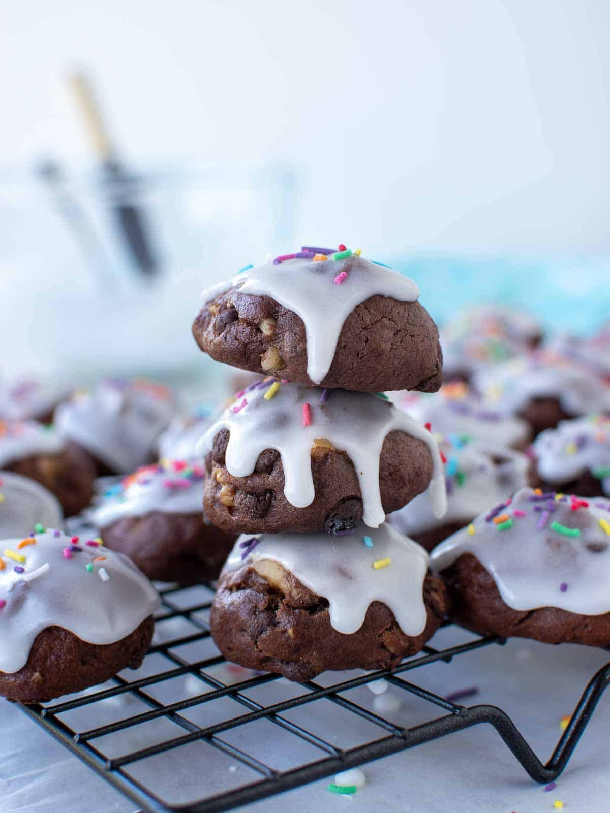 three chocolate cookies with white frosting and sprinkles stacked with extra cookies around all on a wire rack.