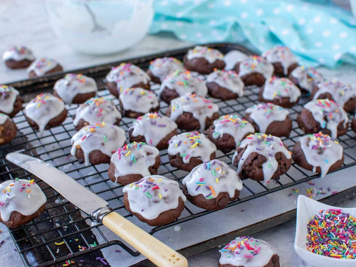 white frosting covered chocolate cookies on wire rack with retro knife.