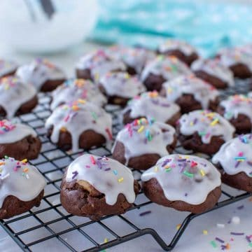 white frosting covered chocolate cookies on wire rack.