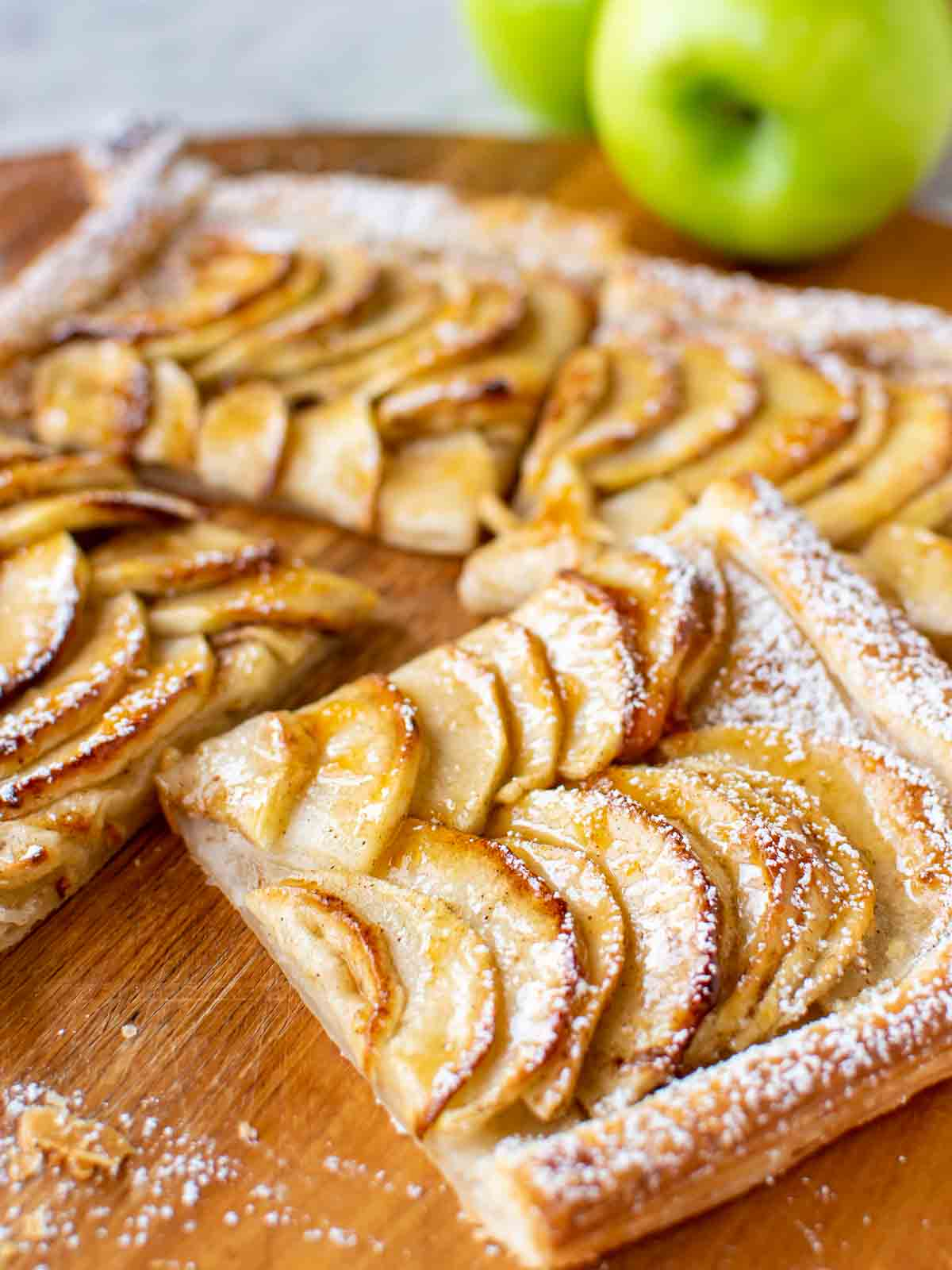 slices of puff pastry apple tart on wooden board, green apple in the background.