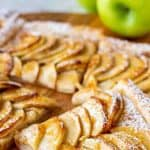 image with text. text reads 'puff pastry apple tart easy. image is slices of puff pastry apple tart on wooden board, green apple in the background.