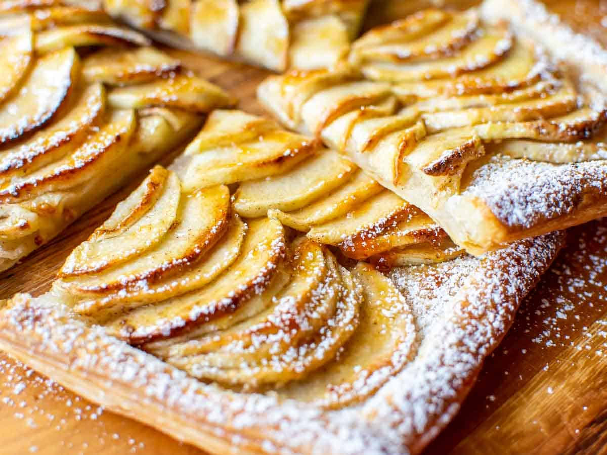 close up slices of puff pastry apple tart on wooden board.