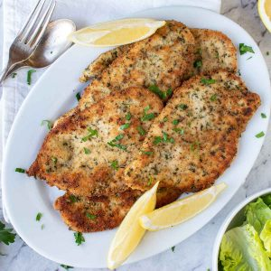 browned chicken cutlets on white plate with lemon wedges viewed from above.