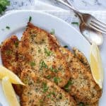 image with text. text reads crispy and tasty italian chicken cutlets. images is browned chicken cutlets on white plate with lemon wedges.