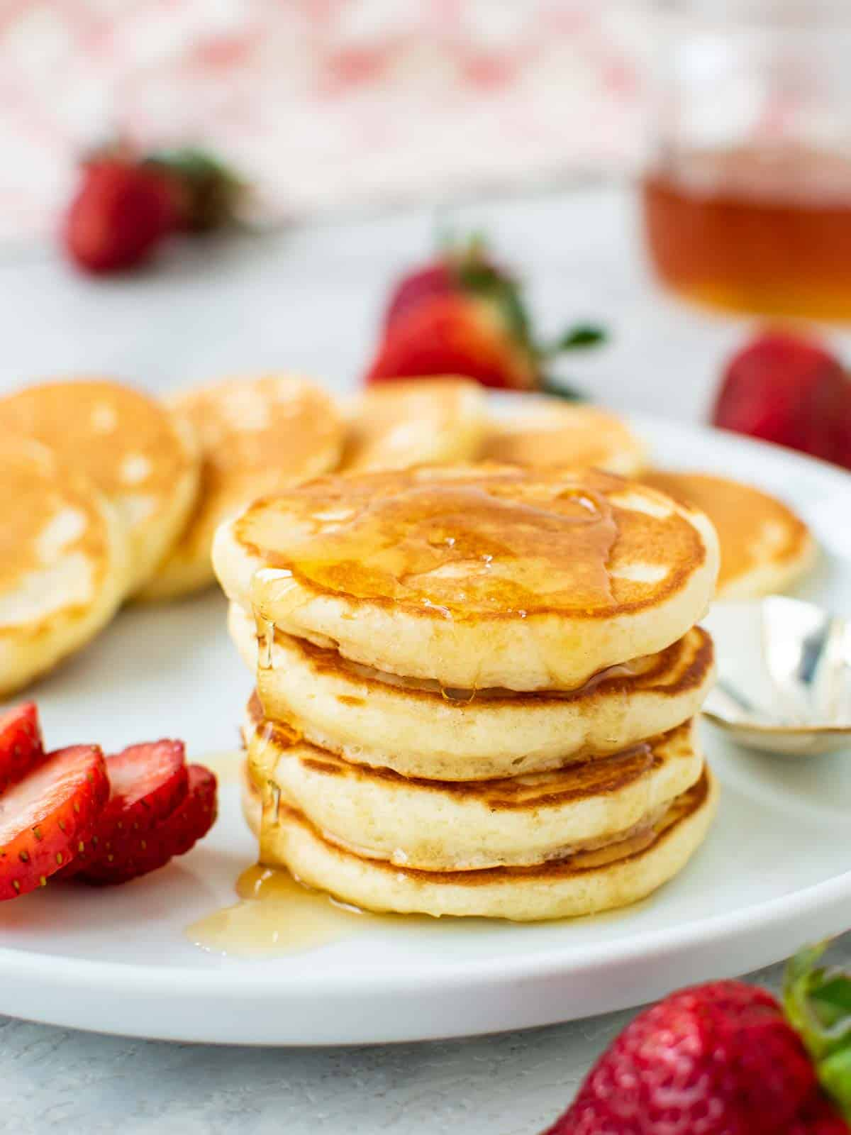 four mini pancakes stacked on a white plate with syrup dripping off and more pancakes and strawberries around.