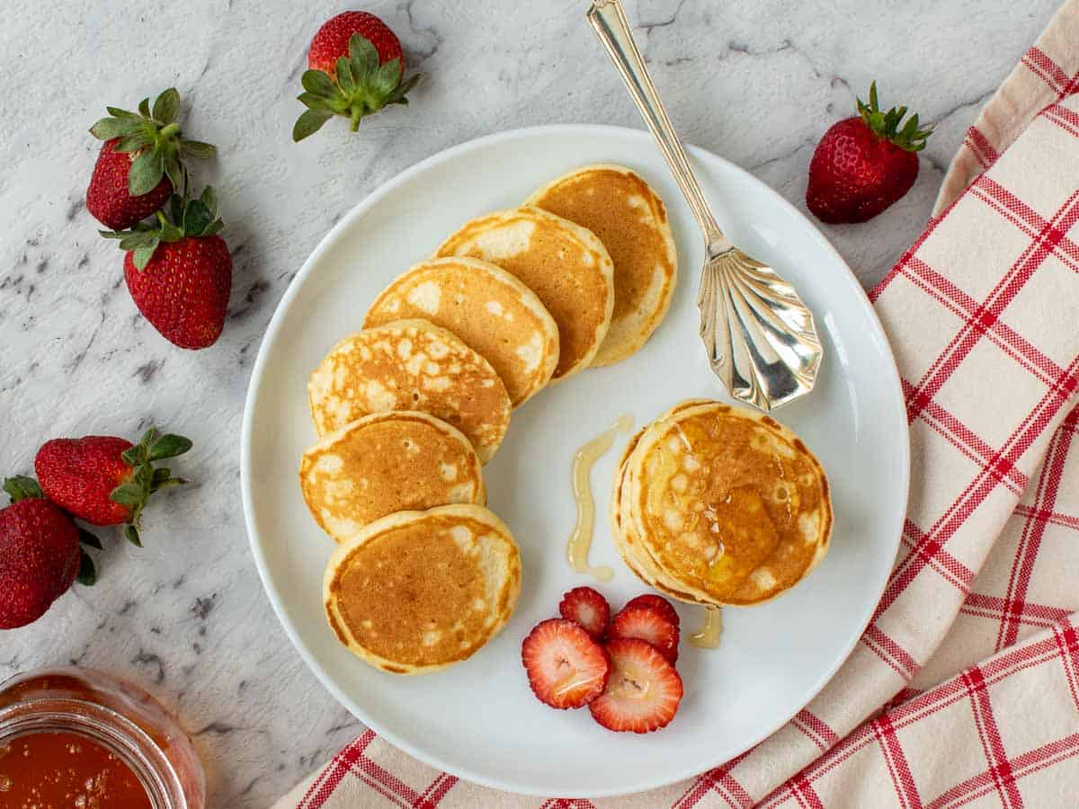 four mini pancakes stacked on a white plate with syrup dripping off and more pancakes and strawberries around viewed from above.