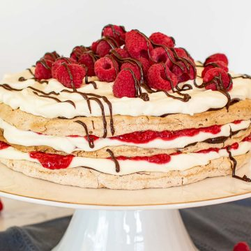 close up of three layer meringue cake with cream, raspberries and chocolate on a white cake stand with raspberries scattered underneath.