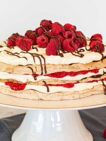 three layer meringue cake with cream, raspberries and chocolate on a white cake stand with raspberries scattered underneath.