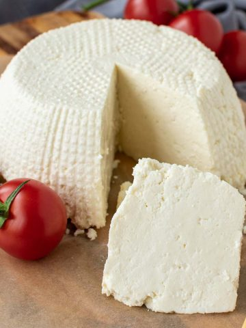 whole fresh ricotta cheese on wooden board with a wedge cut out; wedge in front of whole cheese.