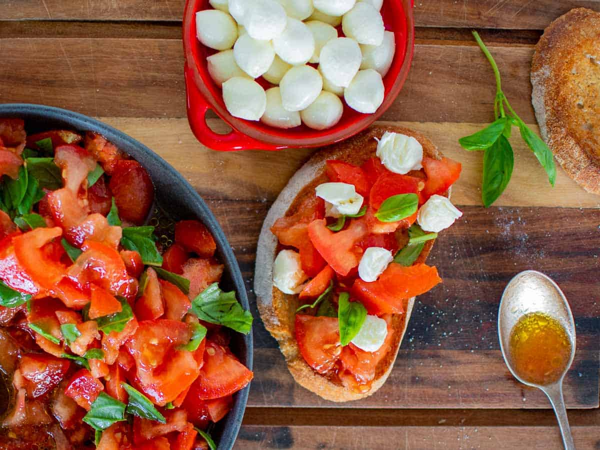 bruschetta with tomatoes and mozzarella, red bowl filled with bocconcini, dark grey bowl with chopped tomatoes and basil, spoon and basil sprig all on wooden board viewed from above.