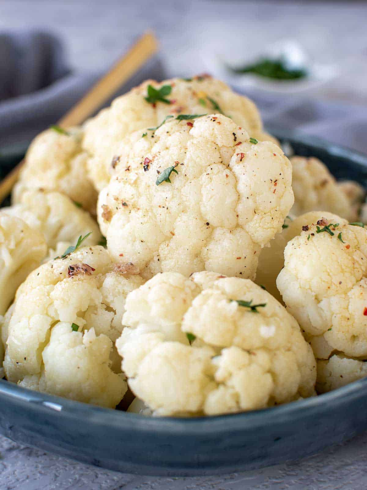 Instant pot cauliflower in a blue bowl on the table ready to eat.
