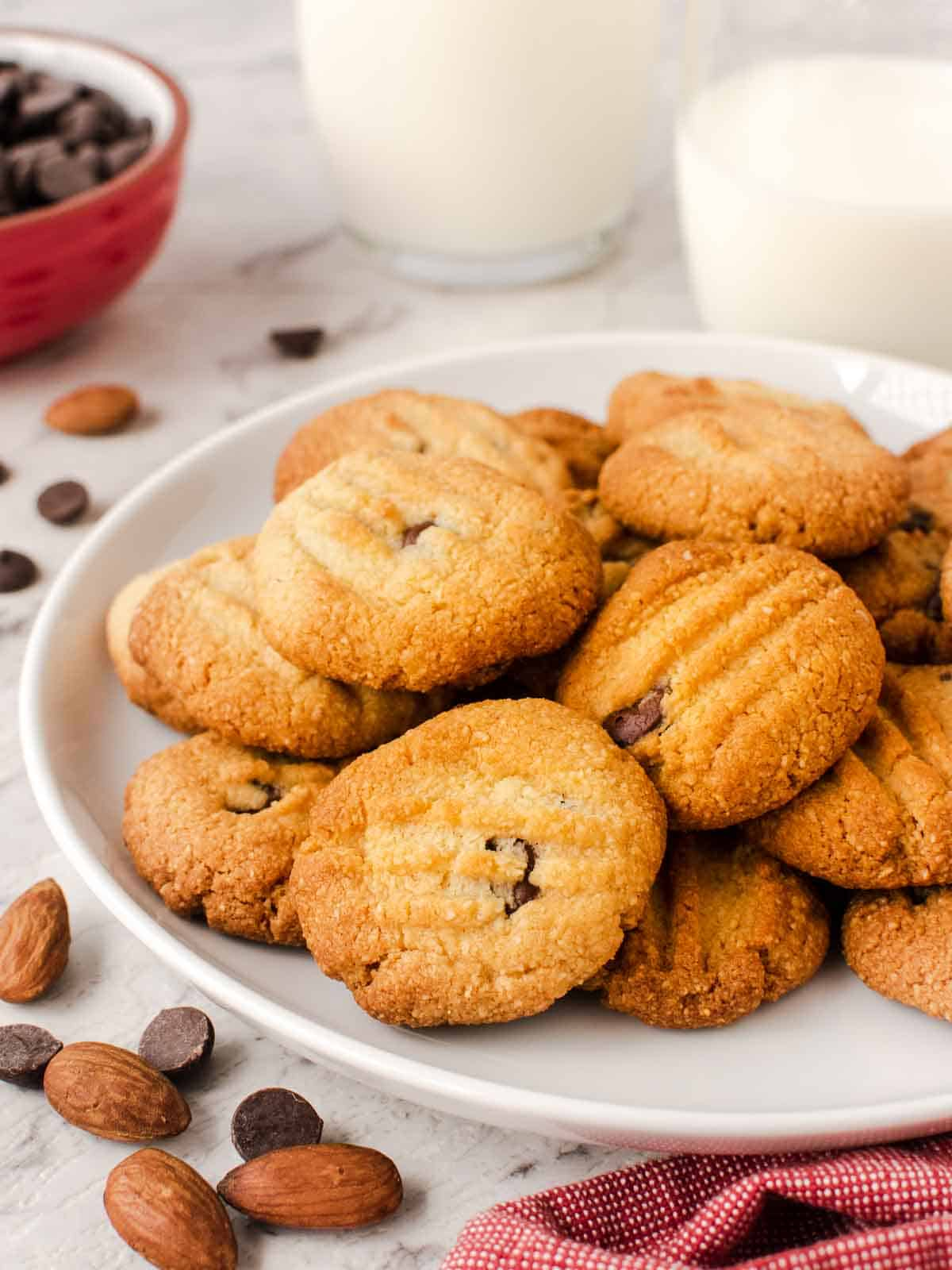 cookies with chocolate bits showing through on a white plate with choc chips and almonds scattered nearby.