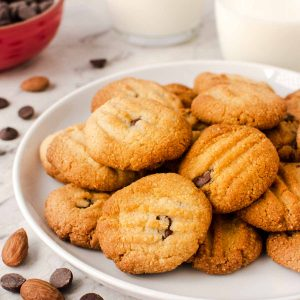 white plate with cookies on and choc chips and almonds scattered nearby.