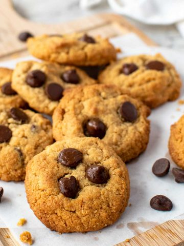 cookies topped with chocolate chips on white baking baking.