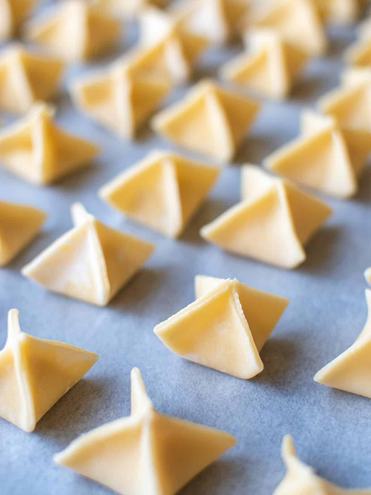 pyramid shaped filled pasta on white baking paper.