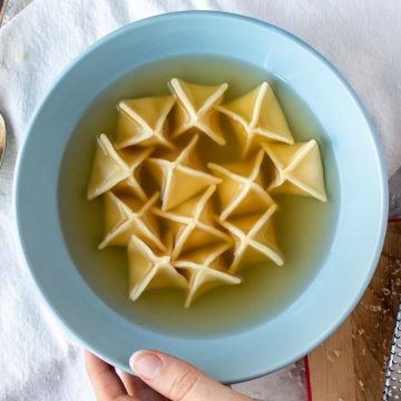 Pyramid shaped filled pasta in broth in blue bowl viewed from above.