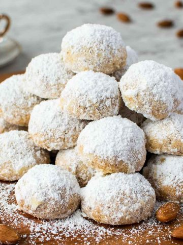 pile of white sugar coated cookies on wooden board with espresso cup in the background.