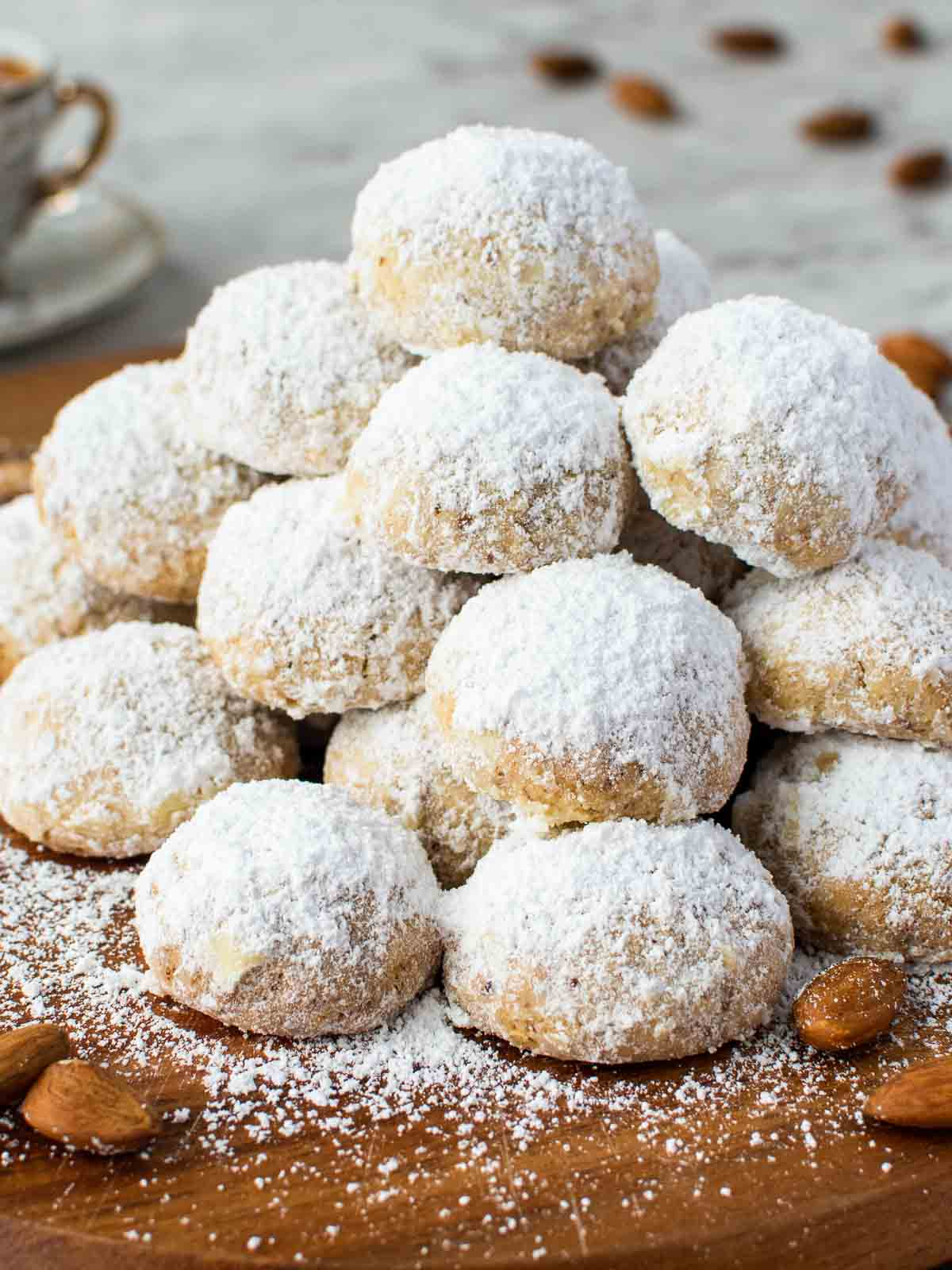 pile of white sugar coated cookies on wooden board.