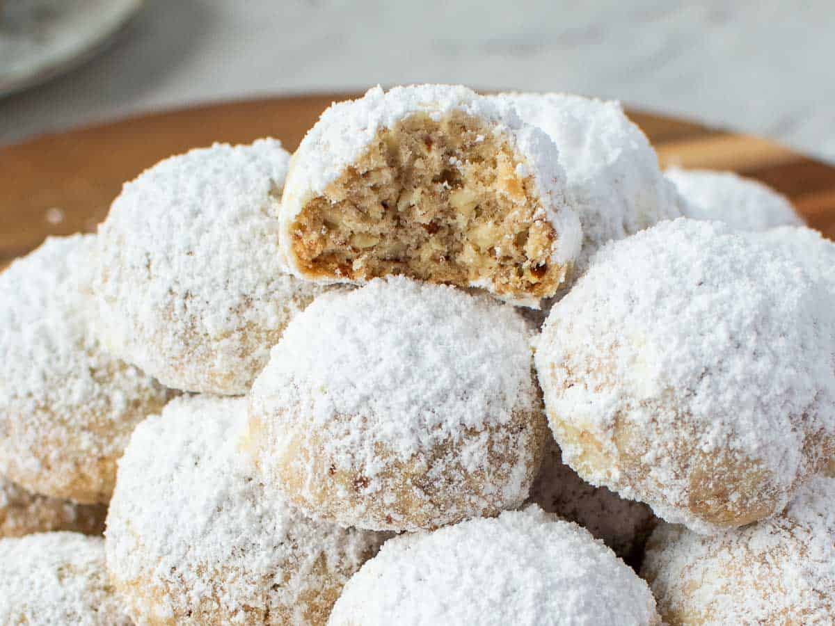 pile of white sugar coated cookies, one cookie at the top with a bite taken out.