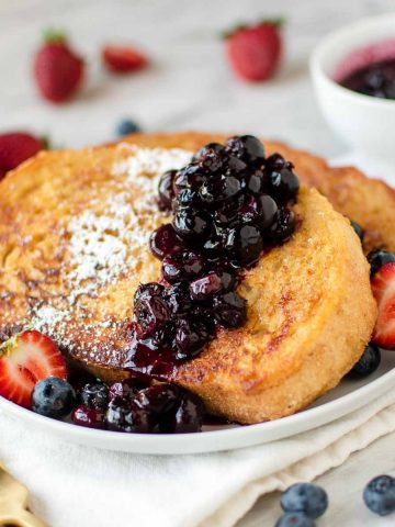 Two slices of sourdough French toast with blueberry compote, powdered sugar, and halved strawberries on a white plate set on a table next to cutlery.