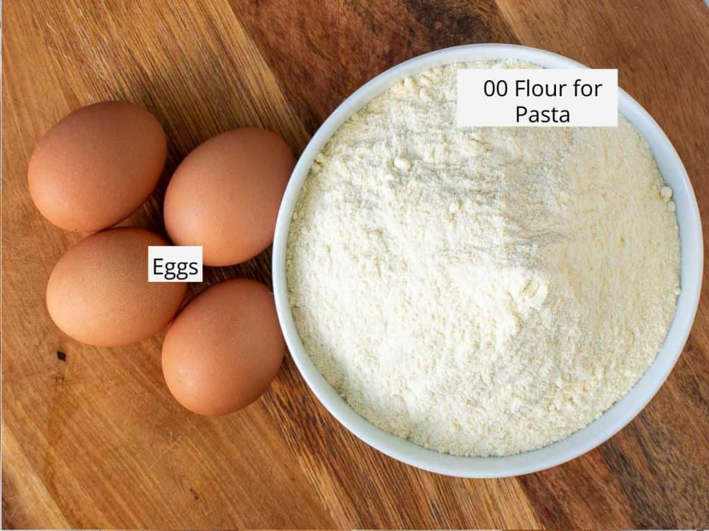 White bowl of flour and 4 eggs on wooden table viewed from above.