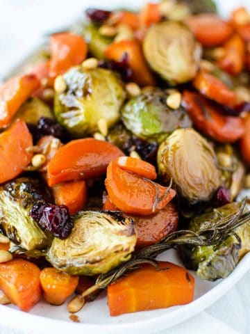 roasted carrots and brussel sprouts on white oblong plate.