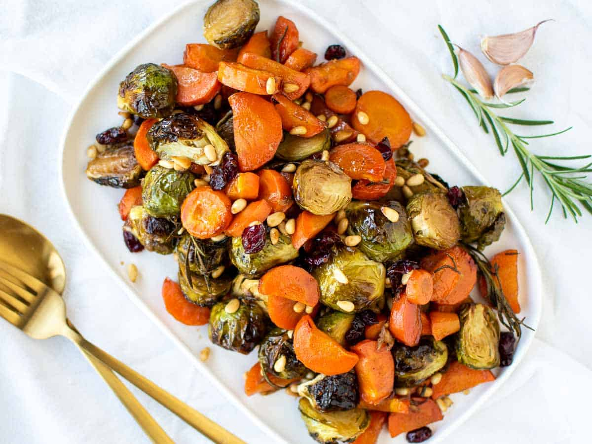 roasted carrots and brussels sprouts on white oblong plate viewed from above.