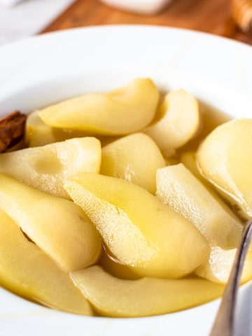 stewed pears in a white large rimmed bowl with spoon.