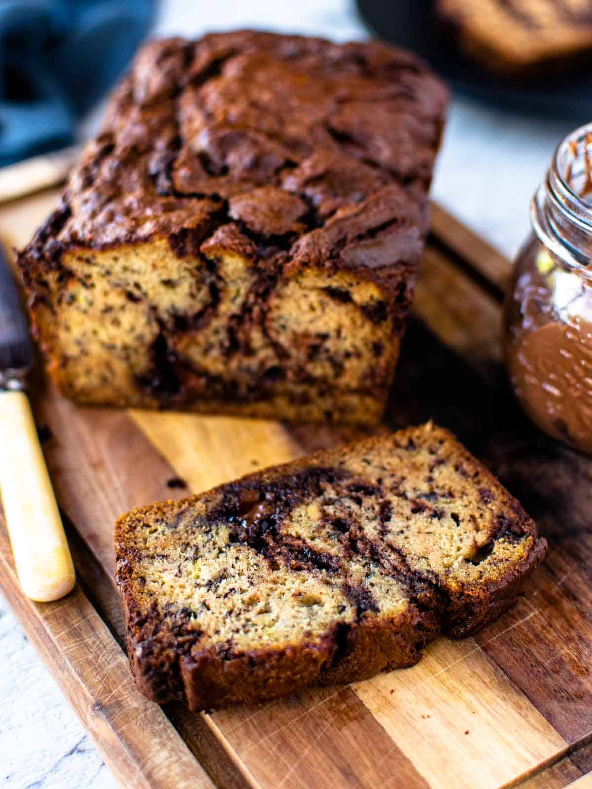 Several slices of baked banana bread with swirls of nutella running through them on a wooden board.